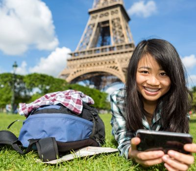 View of a Young attractive asian tourist smartphone tablet in Paris
